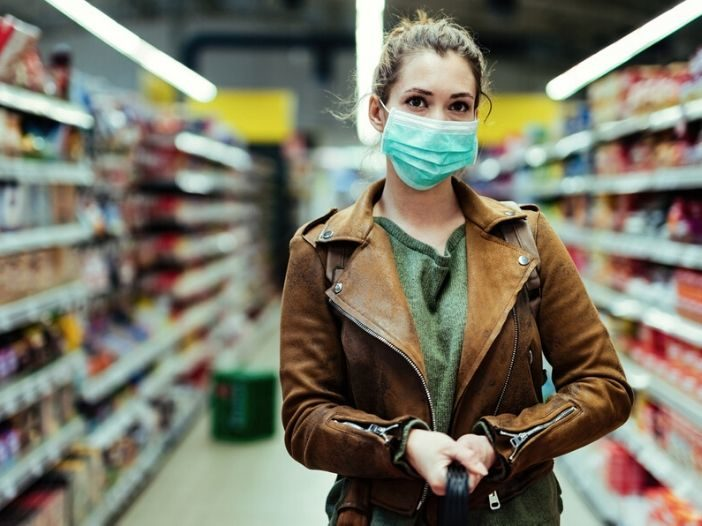 young women socially distancing while wearing a mask in a grocery store